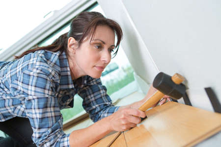 handywoman: good looking red-haired female nailing a plank at home