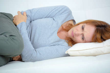 woman on couch: ill sad woman sitting on the couch Stock Photo