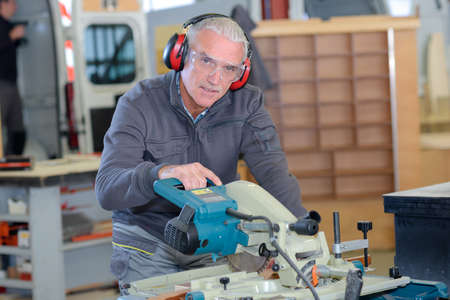 old-man man using a machine in a workshop