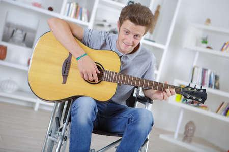 rhythm rhythmic: portrait of cheerful handicapped man with guitar