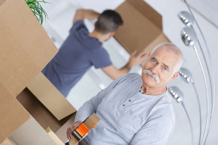 moving box: senior closing a cardboard box as he is moving houses