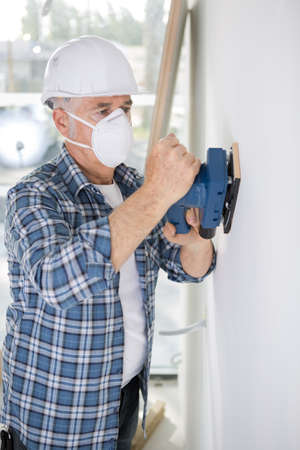 olde man repainting a wall indoors