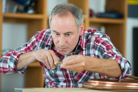 adjusting screw: close up portrait of a middle-age watchmaker at work Stock Photo