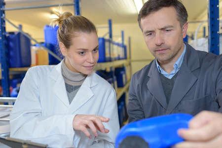 teacher encouraging apprentice using machinery