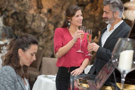pianista: Pareja tostar el champán, acompañado por el pianista Foto de archivo