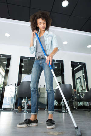 brooming: hairdresser mopping floor in a hair-salon