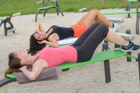 gimnasio mujeres: fitness women doing situps in outdoor gym