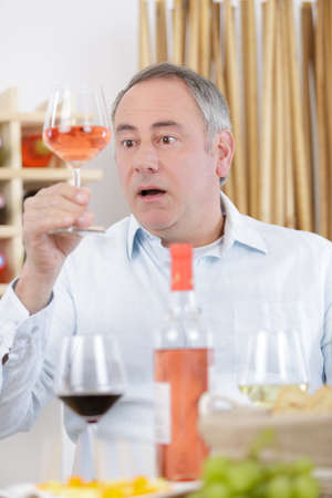 surprised man tasting a glass of rose