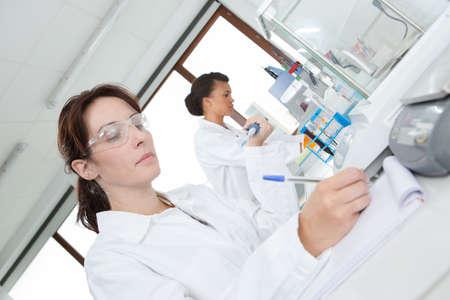 professionele vrouw die beschermende bril in een laboratorium draagt