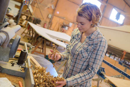 workday: woman carpenter with wood shavings