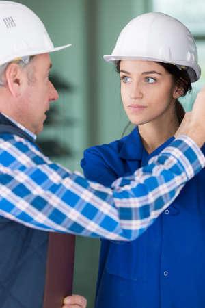 hombres trabajando: técnico de hablar con un joven aprendiz en la fábrica