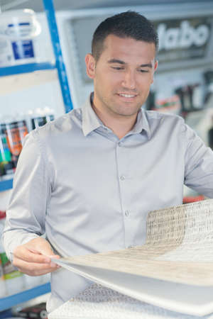 doityourself: man buying wallpaper at hardware store for do-it-yourself project