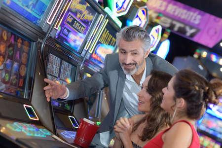 slot machines: grupo de amigos jugando con las máquinas tragaperras