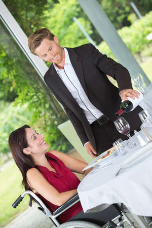 romantic man: man pouring a glass of wine to his handicapped wife