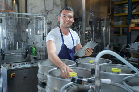 microbrewery: man checking beer in the factory Stock Photo