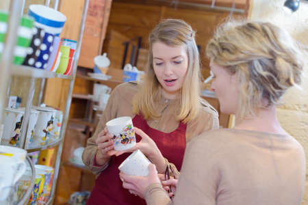 shop assistant of a tea-shop helping customer to choose