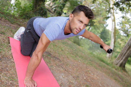 hansome man making exercises on mat outdoors