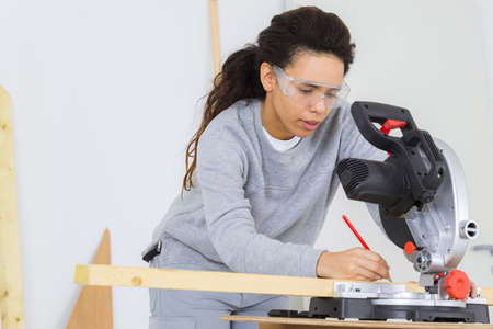 woman sanding a pieces of wood by electric sander diy Stock Photo