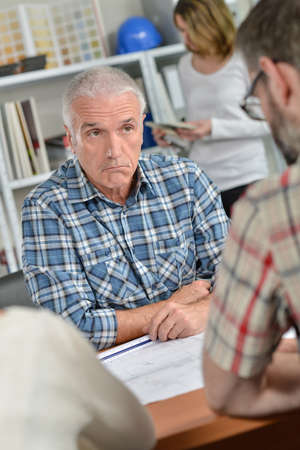 Man in meeting with couple, bemused facial expression Stock Photo