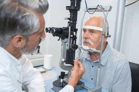 examenes de laboratorio: oftalmólogo hacer un examen ocular en un viejo paciente