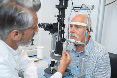 diopter: ophthalmologist doing an eye test on an old patient