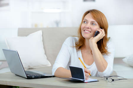 smiling woman making an appointment in a diary Stock Photo