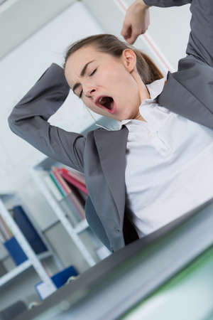 inefficient: sleepy young business woman sitting at office desk Stock Photo