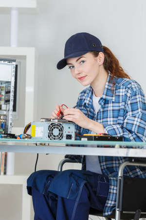 verifying: woman fixing a computer at work Stock Photo