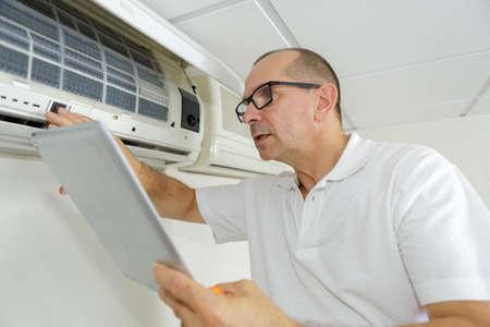 hombre que controla manual de aire acondicionado mientras que la usa