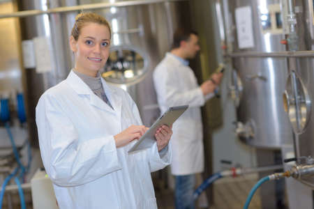 microbrewery: scientist team next to a metal vat in the factory