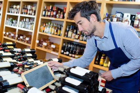 tidying: wine seller man tidying up bottles