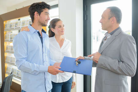 financial planner: real estate agent giving folder to future home owners Stock Photo