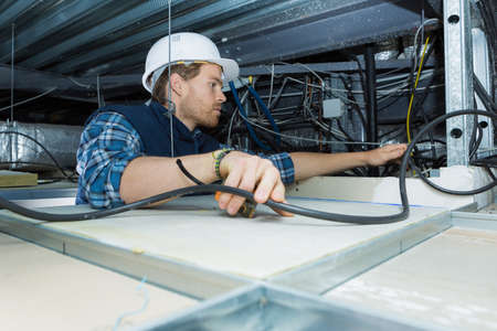 electricity company: electrician fitting a cable for ceiling light