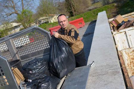 recolector de basura: recolector de basura de carga de bolsas de basura en el camión