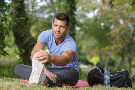 outdoor training: man stretching out muscles in park