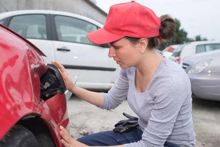 coachwork: coachbuilding sudent working on car in repairshop yard