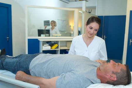 reassure: nurse reassure man in hospital before scanner Stock Photo