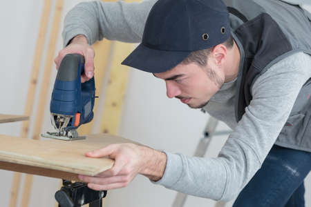 machinery: confident handsome young craftsman in workshop Stock Photo