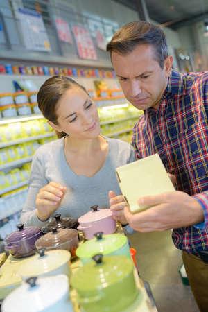 cookware: sonriente pareja familia la compra de vajilla de cerámica en la tienda de utensilios de cocina