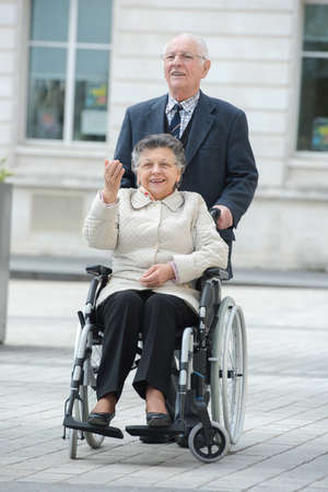 senior man pushing woman in wheelchair in the city