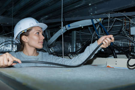 mujer trabajadora: Female contractor passing cables through roof space