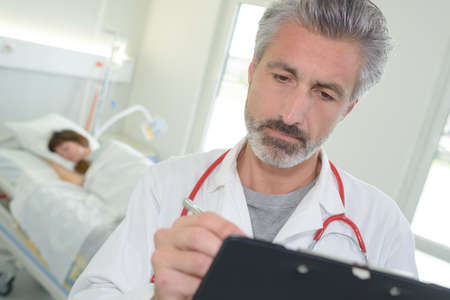private room: portrait of handsome doctor writing on clipboard