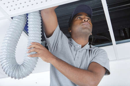 young male electrician on stepladder installing pipes in ceiling