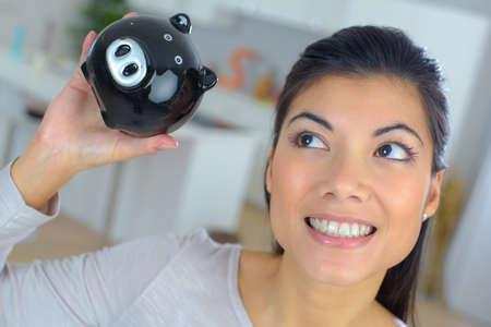 coinbank: wwoman saving money in piggybank