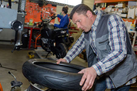 installer: service mechanic with installer replace tyre on wheel in workshop Stock Photo