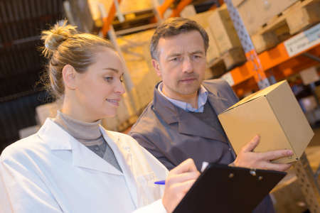 stockpiling: warehouse female worker in uniform checking cardboxes Stock Photo