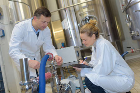 scientists using tablet to control vats in the lab Standard-Bild