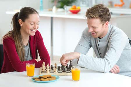 jugando ajedrez: young beautiful couple playing chess indoor