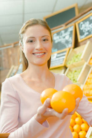 Lady in shop holding three oranges in her hand