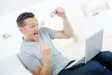 very happy man with laptop Stock Photo